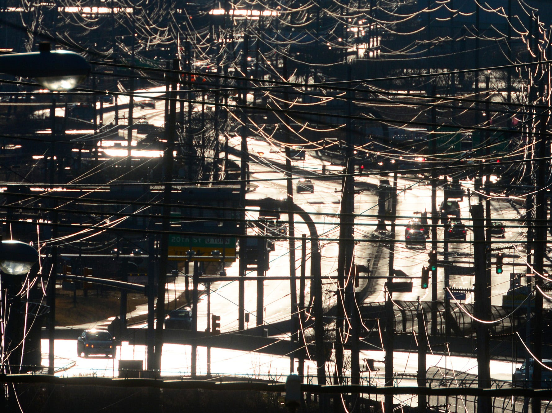 Utility lines and Route 120 in the backlight of the early morning sun on Monday, Febuary 5, 2018.