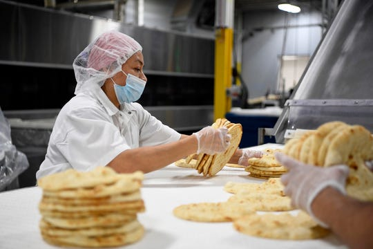 Juani Amador stacks gyro breads for packaging at the Kontos Foods factory on Thursday, Dec. 13, 2018, in Paterson.