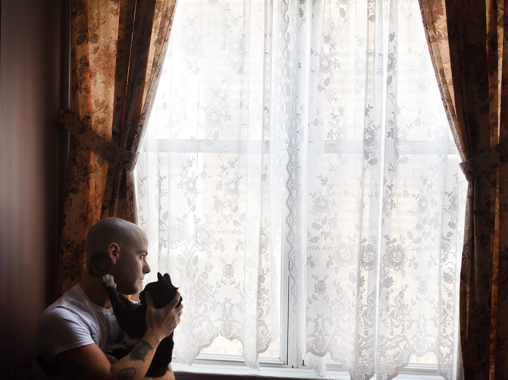 Matt Albanese, a Cliffside Park resident, who was picked up for heroin possession during April's Operation Helping Hand, holds his best friend Ve (16 year-old cat ) as he looks toward the outside from his home in Cliffside Park on 01/02/18. Albanese has stayed clean since his arrest in the sweep, which was done by the Bergen County Prosecutor's Office, and has his life back on track after seven years of addiction.