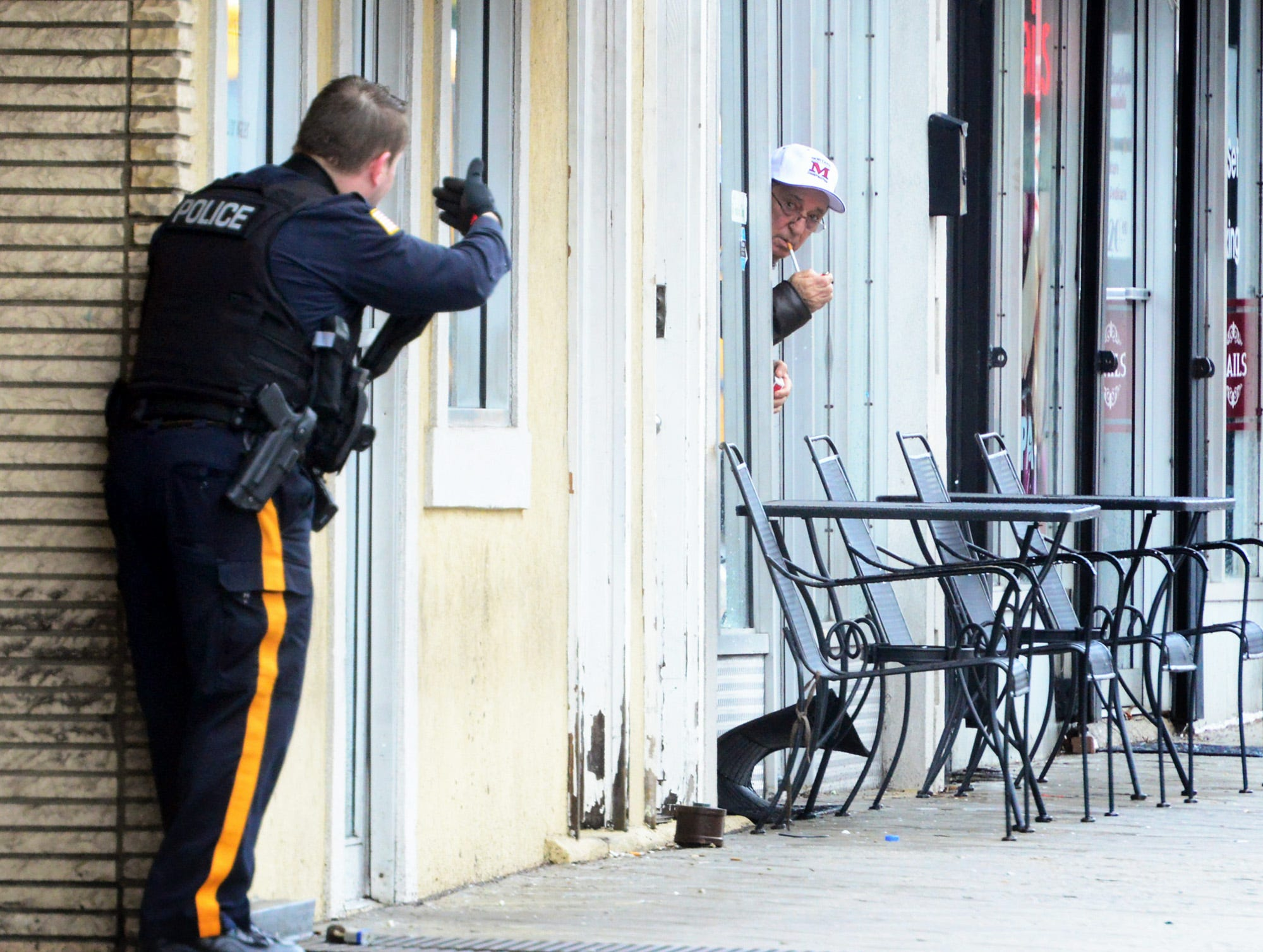 An East Rutherford Police Officer motions to a man trying to sneak a smoke break from a restaurant to get back into the building during the stand off in East Rutherford on Monday April 16, 2018.