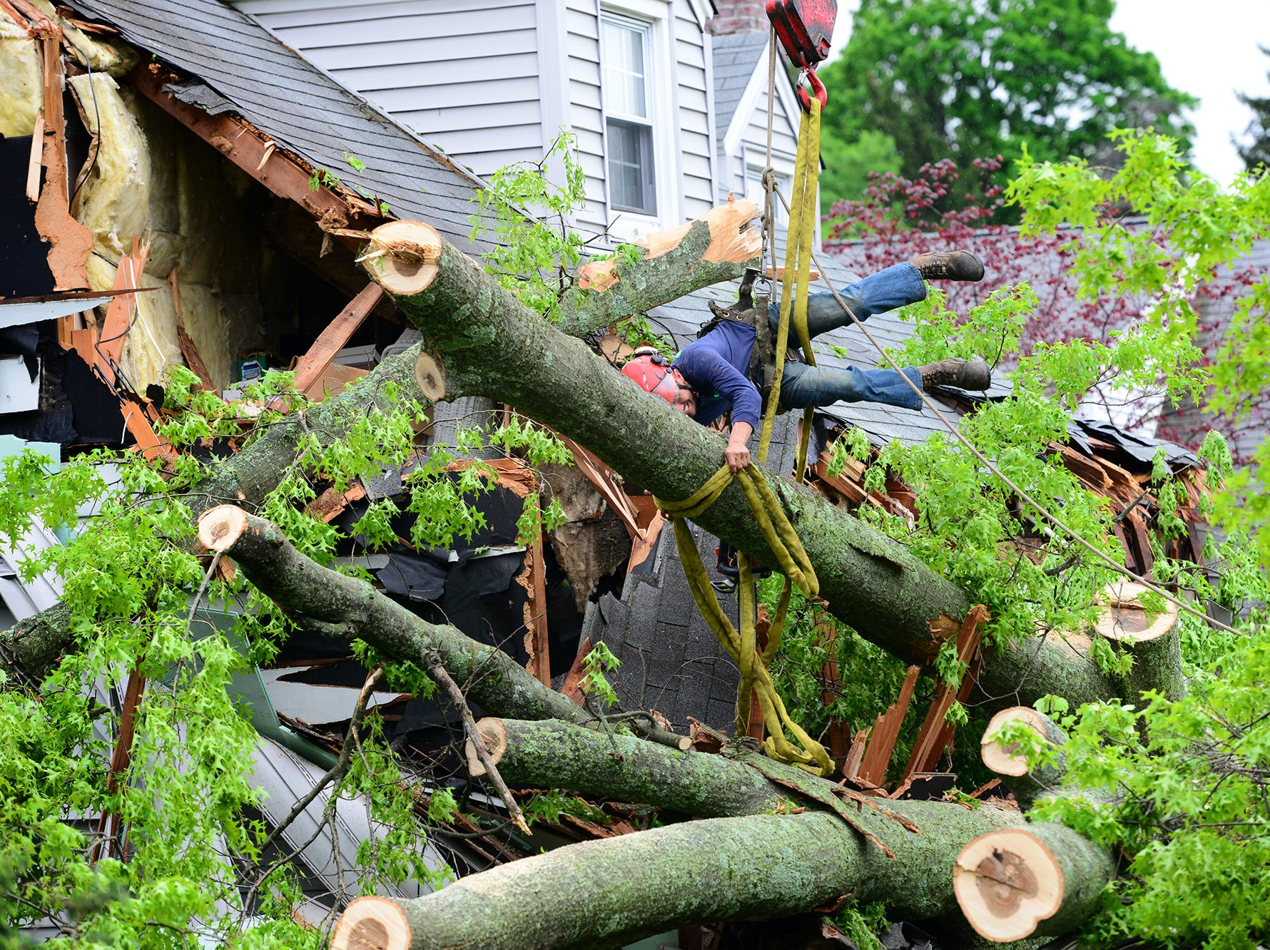 A contractor for a tree removal service clears a tree which uprooted and fell on a house and car at a home on Bernard Place in Ho Ho Kus on Wednesday May 16, 2018. One person was trapped in the car for one and a half hours while they waited for PSE&G to cut the power to the live wires that fell around the car, according to Lisa Brummel, a neighbor.