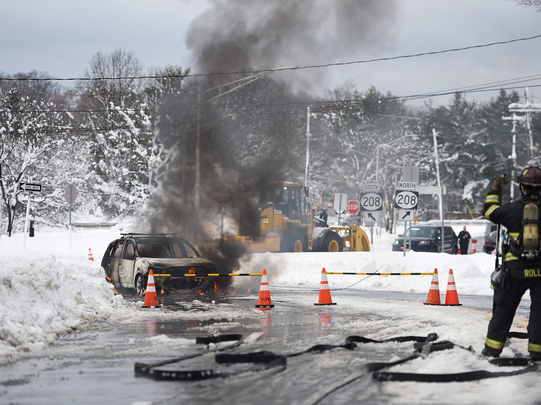 Firefighters stand guard as a car is on fire after electric power line came down on the car, photographed on Summit Ave. near Rt.208 in Franklin Lakes on 03/08/18. No further information is available at this point.