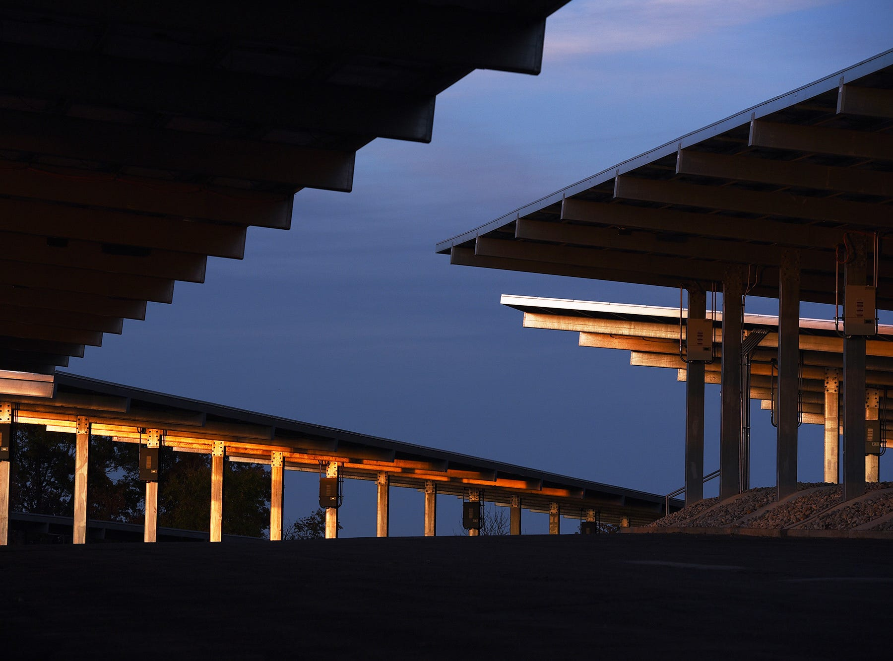Steel beams at the parking lot reflect gold light from the sunset.