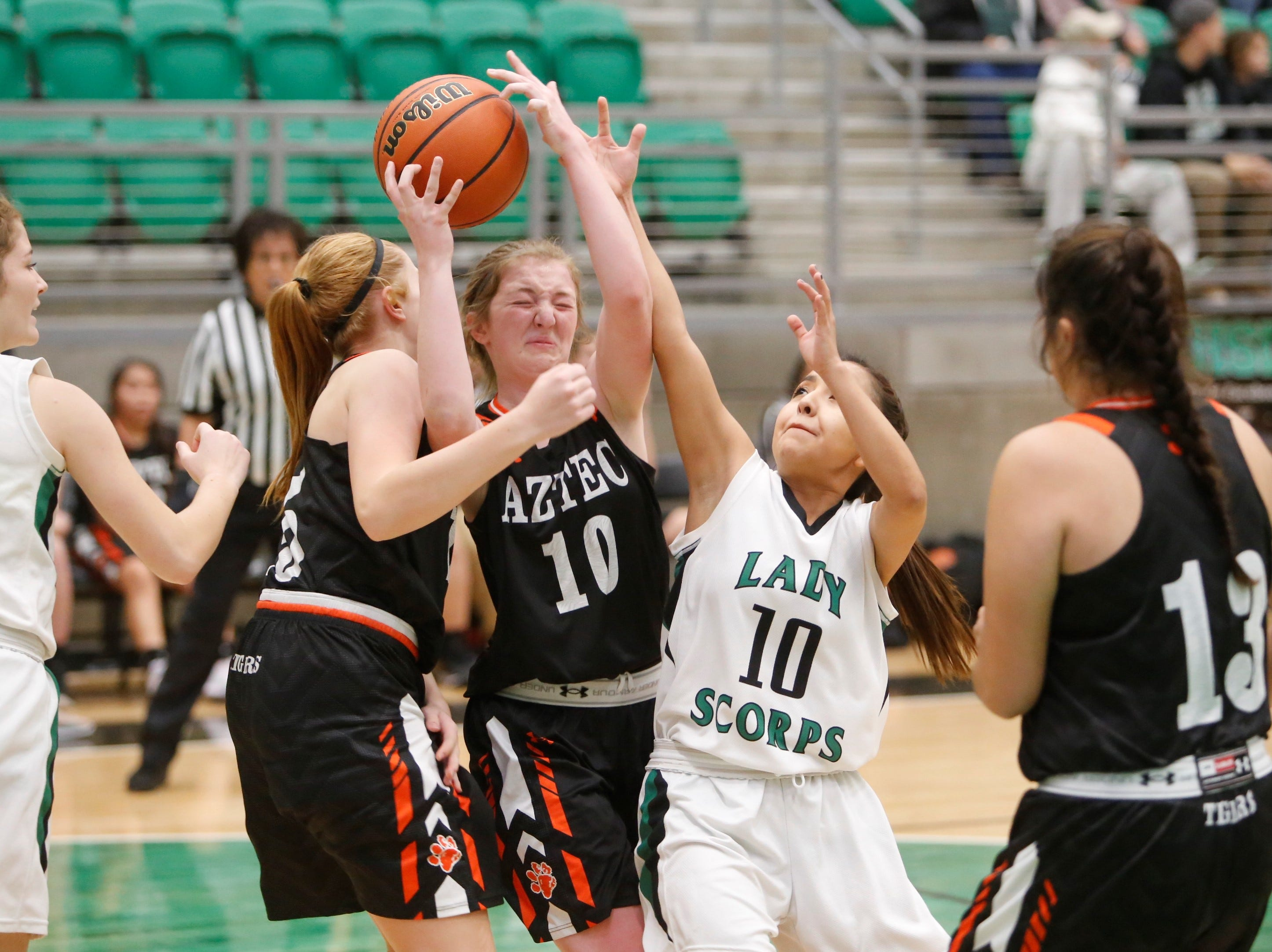 Aztec's Jessi Gillentine (10) pulls down the ball for a defensive rebound against Farmington's Natiana Arviso (10) during Tuesday's game at Scorpion Arena.
