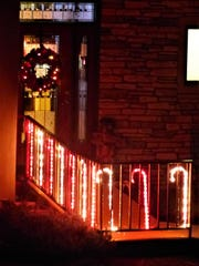 An entry of candy canes invites guests inside at this house.