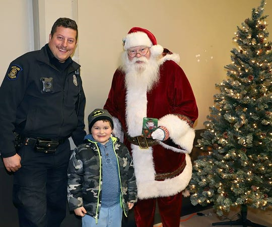 Officer Kevin Yudt and, yes, Santa Claus, pose with a student during the Dec. 11 Shop With a Hero event in Westland. Students were treated to a shopping spree at Meijer, and they and their families joined Westland police officers and firefighters for a pizza party.