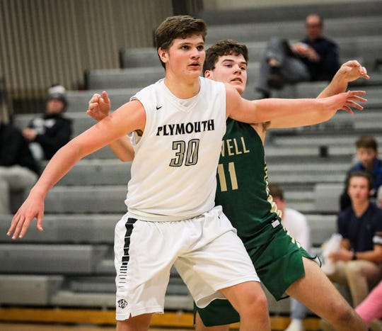 Plymouth's 6-foot-7 Ryan Berger, who scored 14 points, posts upHowell's Michael Brauer (11).