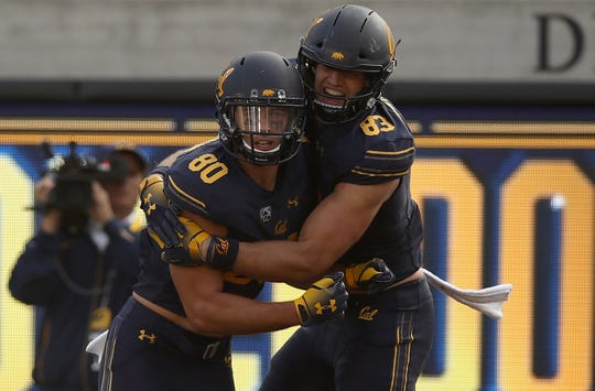 Jake Ashton, left, is congratulated by teammate Ian Bunting after scoring a touchdown against Idaho State on September 15, 2018.