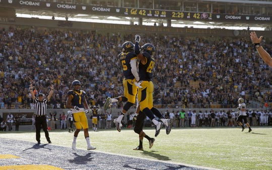 Jake Ashton, right, celebrates with a teammate following a touchdown against Colorado at California Memorial Stadium on September 27, 2014.