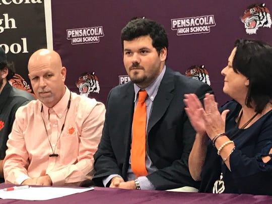 With his parents Bob and Kim looking on, Pensacola HIgh star lineman Hunter Raymond is saluted Wednesday at school reception for signing with Clemson Tigers.