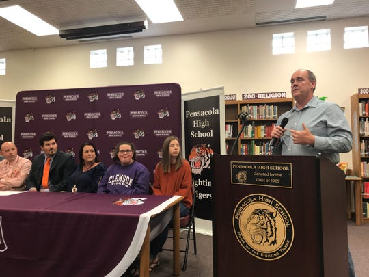 Former Pensacola High coach Mike Mincy speaks about Hunter Rayburn (seated, orange tie) at a reception Wednesday at PHS after Rayburn signed with Clemson.
