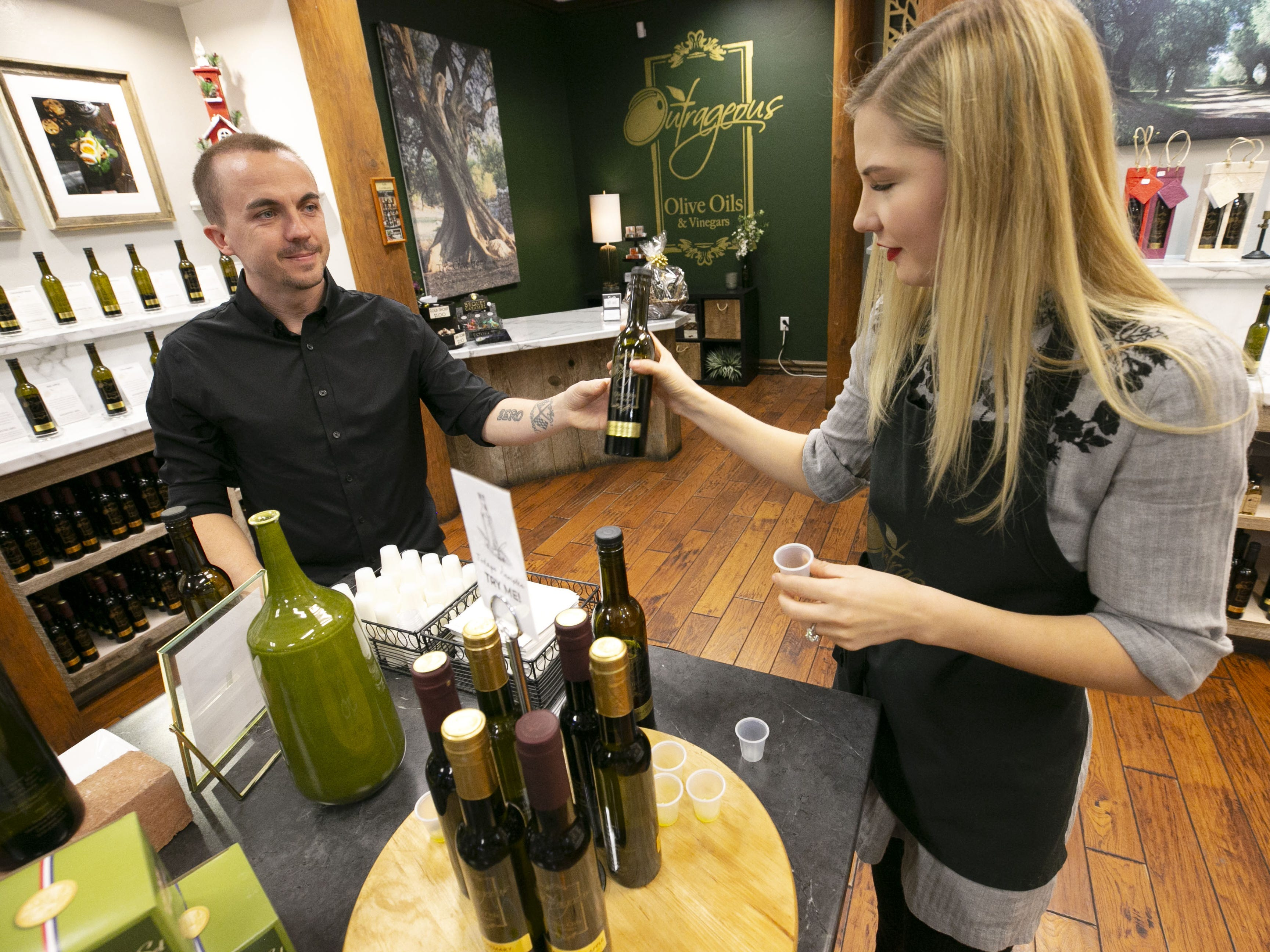 Child actor Frankie Muniz hands a bottle of olive oil to his fiance, Paige Price at their shop, Outrageous Olive Oils & Vinegars in Old Town Scottsdale on Tuesday, Dec. 11, 2018. The couple own and run the store.