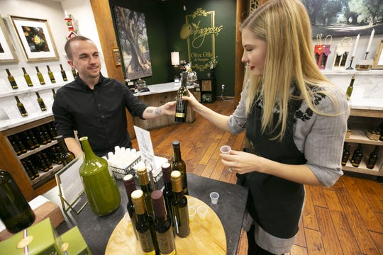 Child actor Frankie Muniz hands a bottle of olive oil to his fiancee, Paige Price, at their shop, Outrageous Olive Oils & Vinegars in Old Town Scottsdale.
