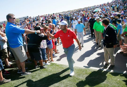 Jon Rahm greets fans while walking towards the 11th tee box at the Waste Management Phoenix Open in Scottsdale, Ariz. Feb. 4, 2018.