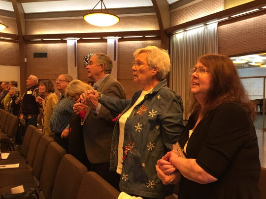 Barbara Cory sings and holds hands with her friend during contemporary worship at Central United Methodist Church.