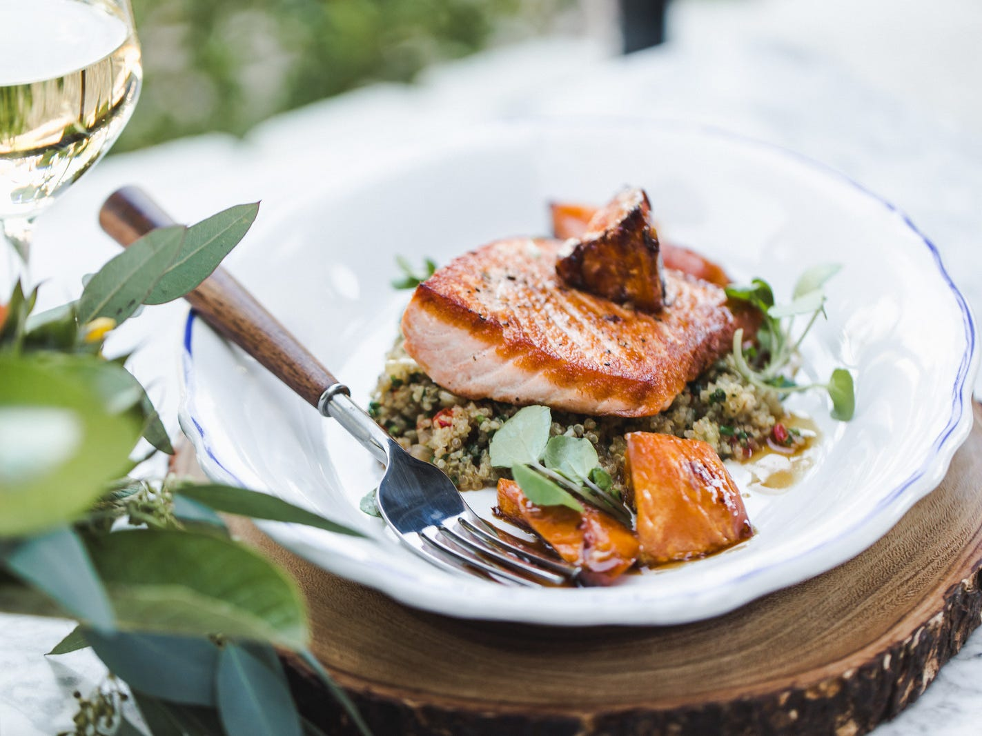Roasted Scottish Salmon with glazed sweet potato, herbed quinoa, and upland cress at Doughbird Pizza & Rotisserie.