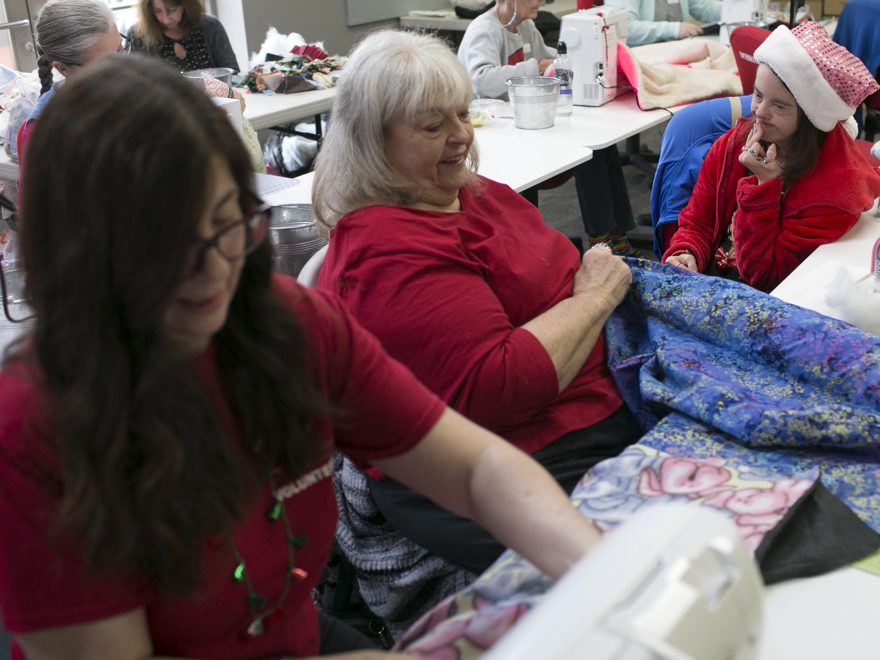Debbie Lemon (left) teaches a class on how to make dog beds for animal shelters at the Bernina Connection with her mother, Valerie Friel (center), and her sister, Lindsy Friel (right), joining on Dec. 15, 2018, at the Bernina Connection.