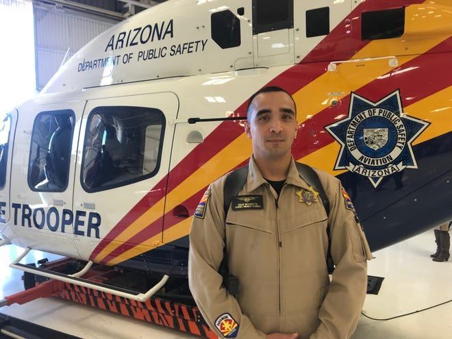 Arizona DPS air-rescue paramedic Edgar Bissonnette poses near the Bell 429 helicopter, their newest aircraft that has advanced hoist technology. In November it allowed Bissonnette and two other crew members to save a 52-year-old man stranded on a mountain north of Sedona.