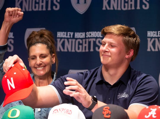 Higley defensive lineman Ty Robinson celebrates with his mom, Tresha, after he announces he will be attending University of Nebraska during signing day at Higley High in Gilbert on Dec. 19, 2018.