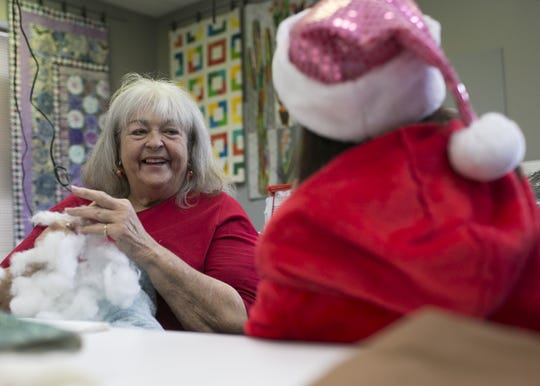 Valerie Friel (left) smiles at her daughter Lindsy Friel (right) as they make dog beds for animal shelters at the Bernina Connection on Dec. 15, 2018.
