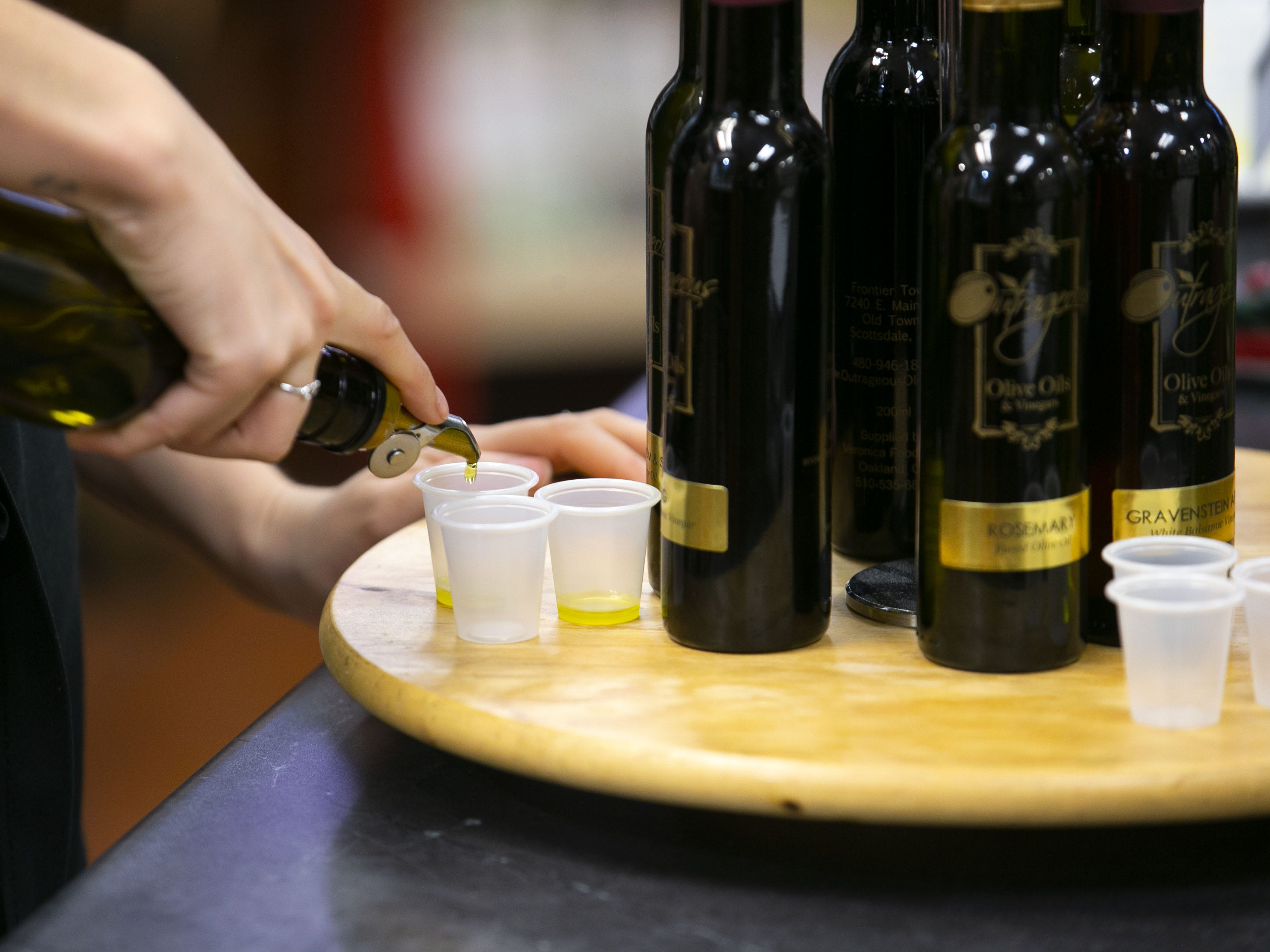 Samples of olive oil are poured at Outrageous Olive Oils & Vinegars in Old Town Scottsdale on Tuesday, Dec. 11, 2018. The shop is owned by former child actor, Frankie Muniz and his fiance Paige Price.