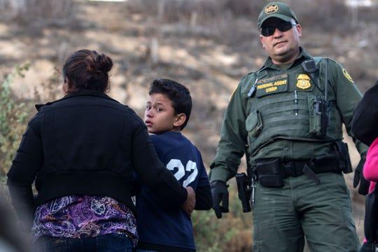 Un agente de la Patrulla Fronteriza habla con un grupo de migrantes sorprendido cruzando la frontera.