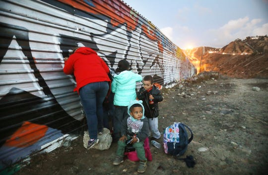TIJUANA, MEXICO - DECEMBER 01:  Honduran migrants gather on the Mexican side of the U.S.-Mexico border fence after some unsuccessfully attempted to cross into the U.S. on December 1, 2018 in Tijuana, Mexico. Mexican police detained the group on the Mexican side of the barrier and said they would return the group to a new government shelter, located far from the border, for members of the 'migrant caravan'. Many of those in the caravan traveled for over a month from Central America to seek asylum in the U.S. (Photo by Mario Tama/Getty Images)