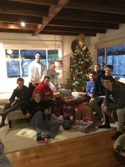 Cedar Crest's boys basketball team poses with the gifts they purchased and wrapped for a family in need in the school district.