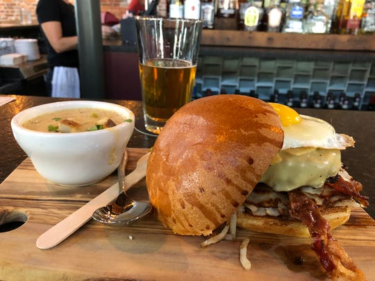 """""""The Conspiracy Burger"""" at Rising Sun, a burger with hash brown, bacon and egg, shown here served with seafood chowder and pint."""