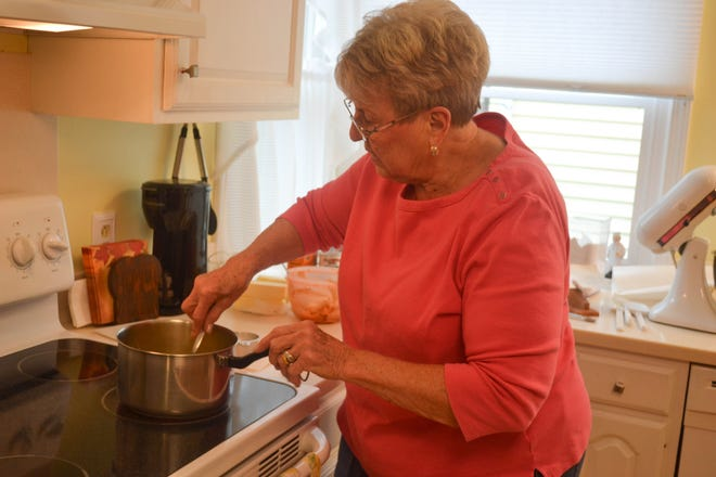 Sandy Konieczny stirs the cinnamon swirl for Herman Cakes on her stovetop.