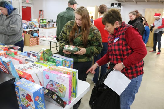Sherila Carter, right, helps Shelby Jennings pick out games for her 5-year-old son during the local Salvation Army's annual Toys for Tots distribution.