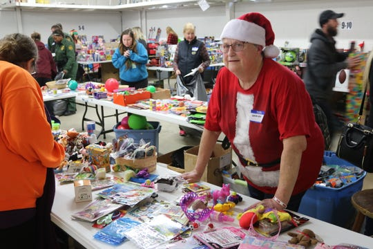 "ShirLee Eberle volunteers at the ""stocking stuffer"" table during the local Salvation Army's annual Toys for Tots distribution."