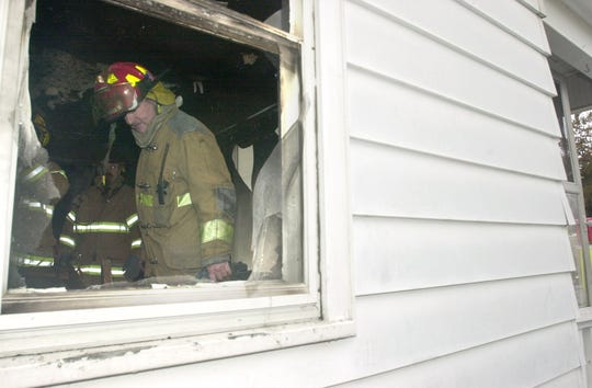 Firefighters poke through the remains of a Port Huron home after a Christmas tree fire in 2002 damaged the house.