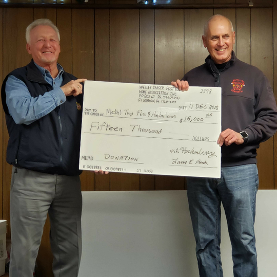 American Legion Wesley Yeager Post Home Association President Bill Hockenberry presents a $15,000 check to Dale Hall of the Metal Township Fire and Ambulance Squad.