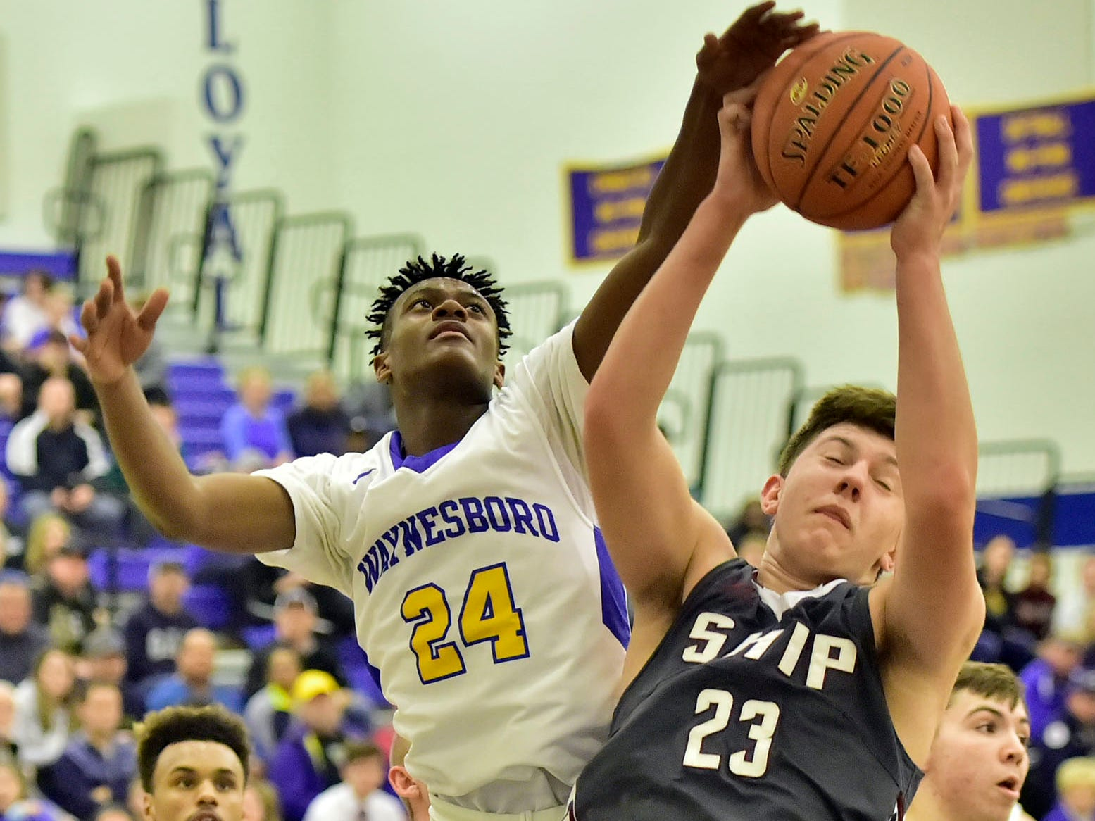 Shippensburg's Collin Taylor (23) grabs a rebound over Waynesboro's Jerem Brown (24) on Tuesday, December 18, 2018. Waynesboro defeated Shippensburg 72-59 during a home game.