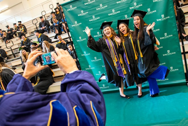 From left, Morgan Scheler, Julie Heisey and Mary Hurd pose for a picture taken by Dr. Fred Becker prior to graduation. York College graduated nearly 300 during its 2018 winter commencement, held at the Grumbacher Sport and Fitness Center's M&T Field House.