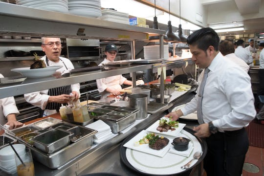 Chef Jacinto Guadarrama, left, prepares dishes with the help of the kitchen staff at Gotham Bar and Grill in New York on Nov. 27. Restaurant sales, always a leading indicator of consumer health, were down at a 3.6 percent annual rate in November.