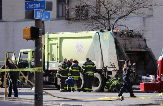 Firefighters work on a person struck by a Rochester garbage truck Wednesday.