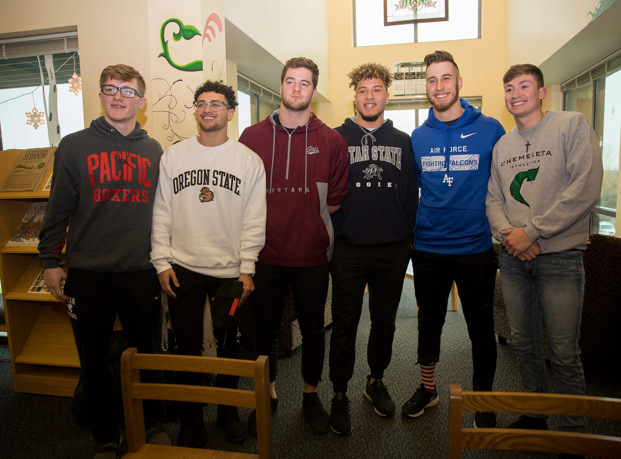 West Salem High School senior athletes pose after signing to their respective colleges in the school library on Wednesday, Dec. 19, 2018.