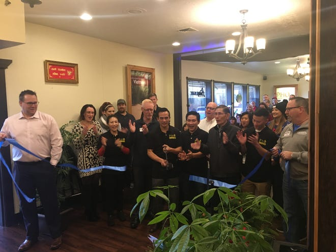 Teresa and Jonathon Pham cut a ribbon to celebrate the opening of their new restaurant, Pho Keizer, alongside members of the Keizer Chamber of Commerce on Dec. 18, 2018.
