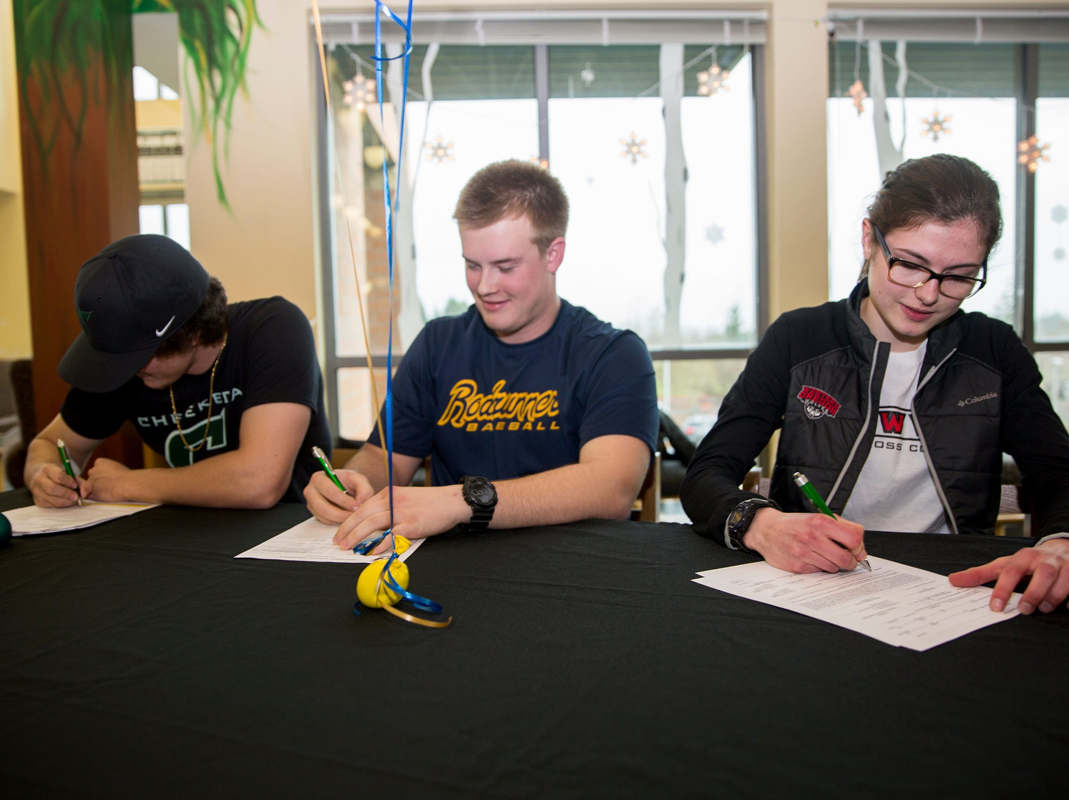 Brandon Allison, Lucas Stanfield and Jaden Mandal sign to their respective colleges in the school library on Wednesday, Dec. 19, 2018.
