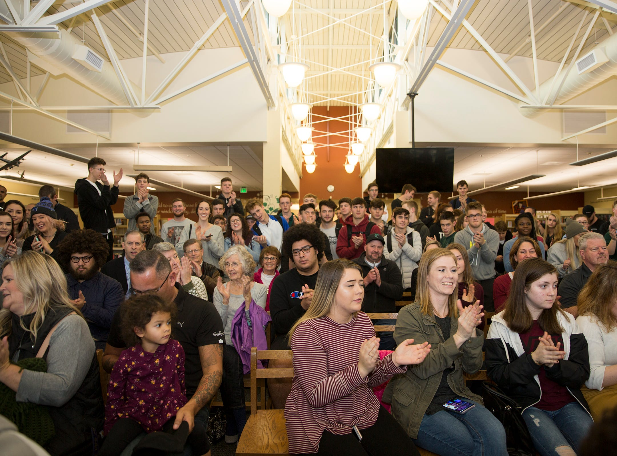 Friends and family of 10 West Salem High School seniors support them as they sign to their respective colleges in the school library on Wednesday, Dec. 19, 2018