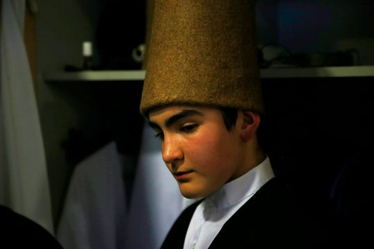 In this photo taken on Sunday, Dec. 16, 2018, a young whirling dervish of the Mevlevi order concentrates in the locker room prior to a Sheb-i Arus ceremony in Konya, central Turkey. Every December the Anatolian city hosts a series of events to commemorate the death of 13th century Islamic scholar, poet and Sufi mystic Jalaladdin Rumi.