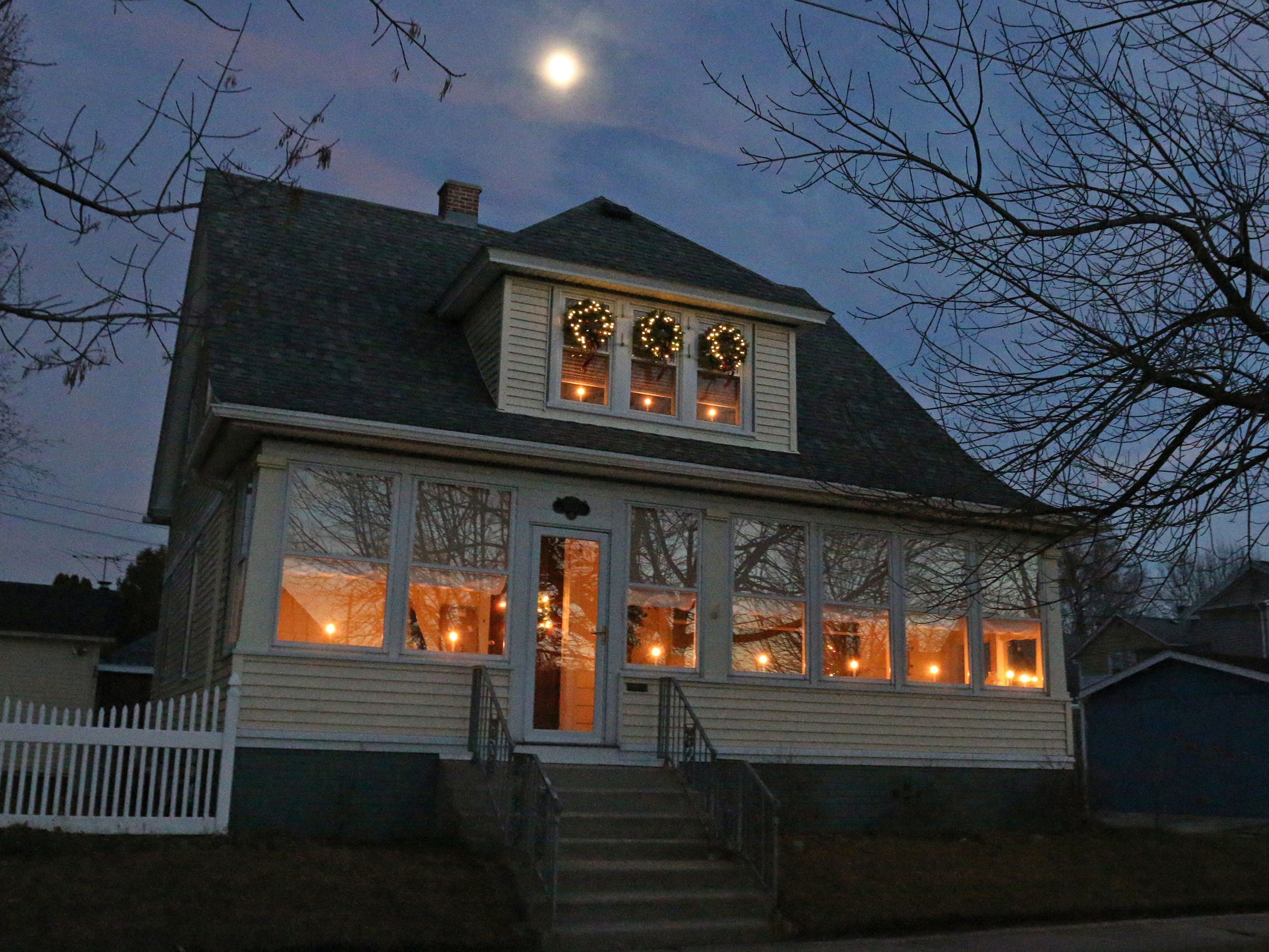 A home features lit holiday lights with the moon overhead on North 1st Street, Tuesday, December 18, 2108, in Sheboygan, Wis.