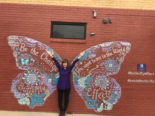 Judy Williams poses in front of the mural at 300 North Allen St. where a giant butterfly was painted to inspire micro-philanthropy. The nonprofit,  The Butterfly Effect, will make a donation to charities individuals tag in photos of the mural.