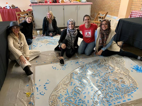 A crew of local women and girls paitned a giant butterfly on the side of 300 North Allen Street.