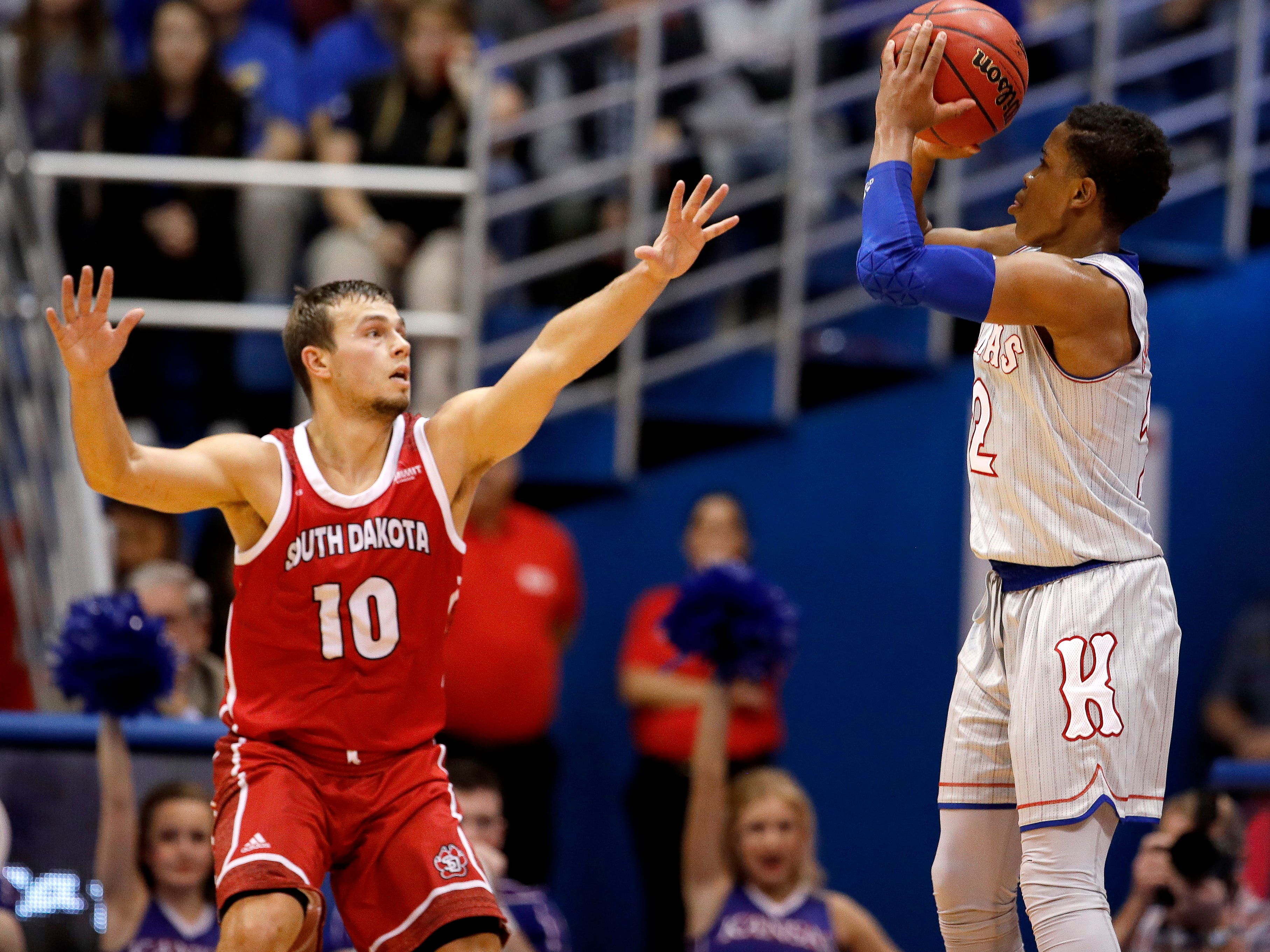 Kansas' Charlie Moore, right, shoots over South Dakota's Cody Kelley (10) during the second half of an NCAA college basketball game Tuesday, Dec. 18, 2018, in Lawrence, Kan. Kansas won 89-53. (AP Photo/Charlie Riedel)
