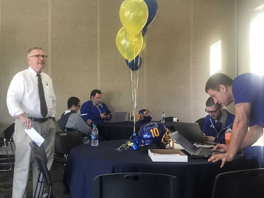 SDSU coach John Stiegelmeier (L) and recruiting coordinator Dan Jackson (far right) put the finishing touches on signing day Wednesday morning in the Champions room of the SDSU football offices.