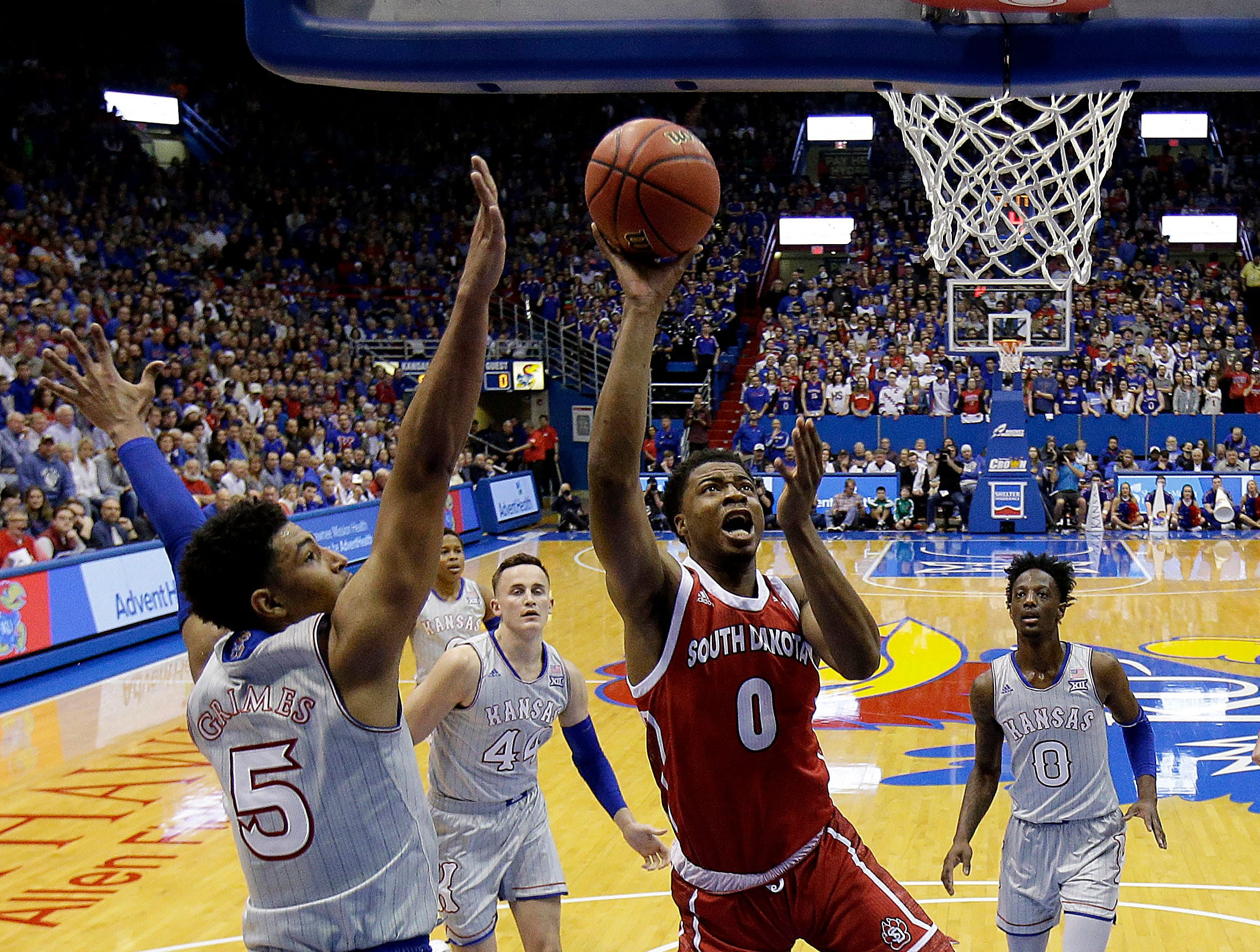 South Dakota's Stanley Umude (0) puts up a shot under pressure from Kansas' Quentin Grimes (5) during the first half of an NCAA college basketball game Tuesday, Dec. 18, 2018, in Lawrence, Kan. (AP Photo/Charlie Riedel)