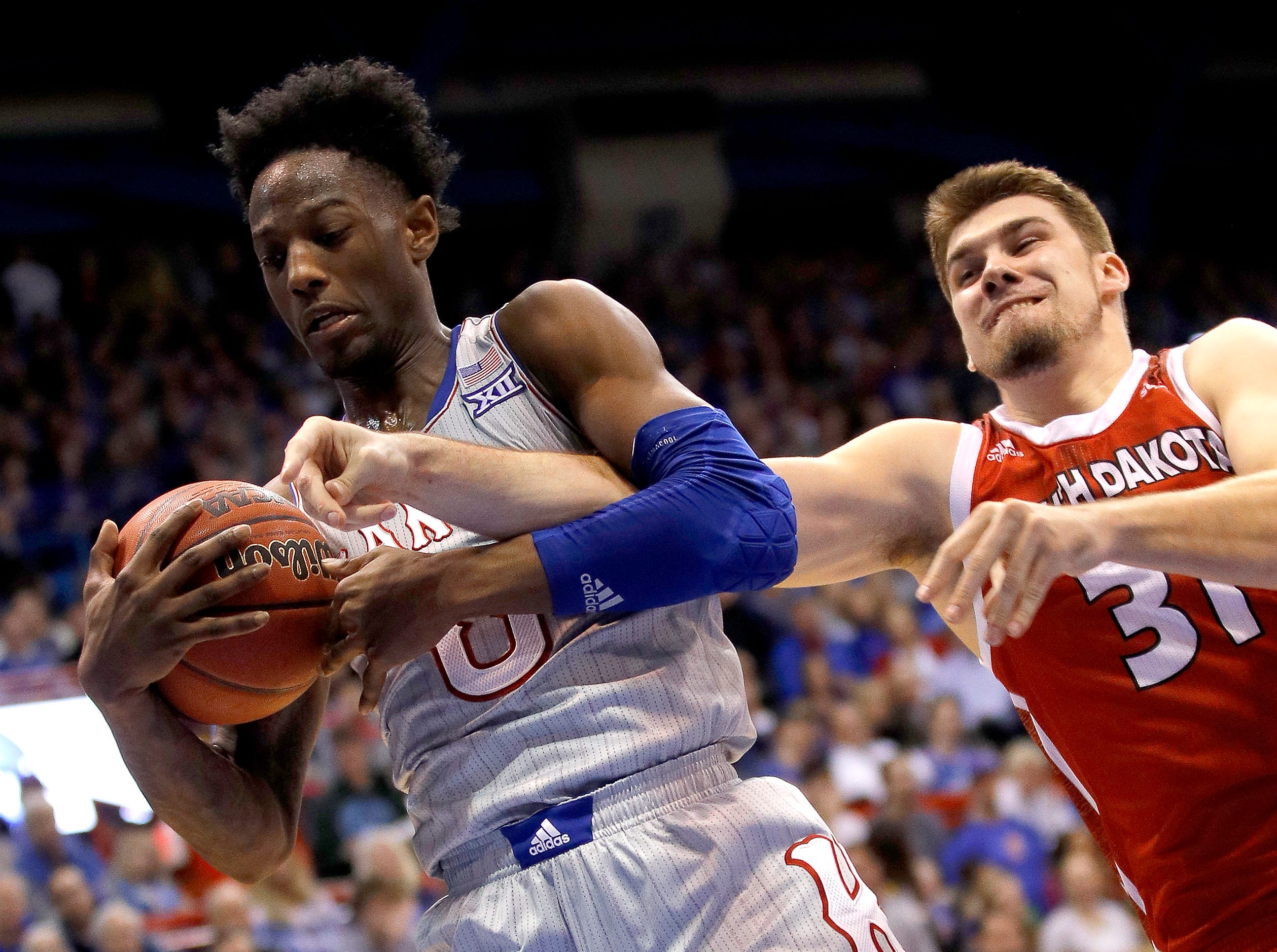 South Dakota's Dan Jech (31) tries to steal the ball from Kansas' Marcus Garrett (0) during the second half of an NCAA college basketball game Tuesday, Dec. 18, 2018, in Lawrence, Kan. Kansas won 89-53. (AP Photo/Charlie Riedel)